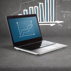 A laptop with a graph displayed on the screen. In the background is a bar graph.